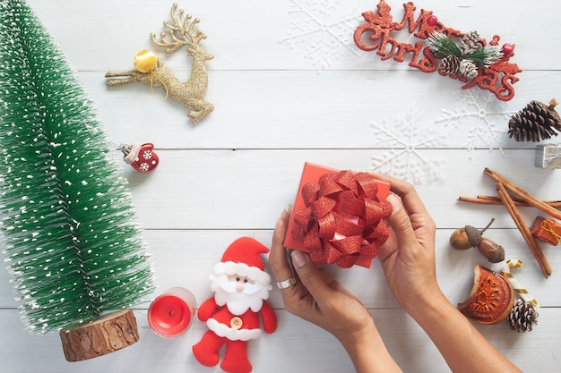 白い木製のテーブルトップにクリスマスギフトボックスを保持している女性の手の上面図