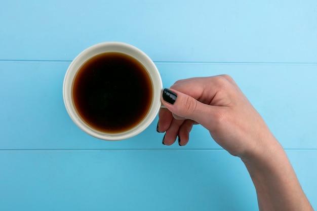 青の背景にお茶のカップを保持している女性の手の上から見る