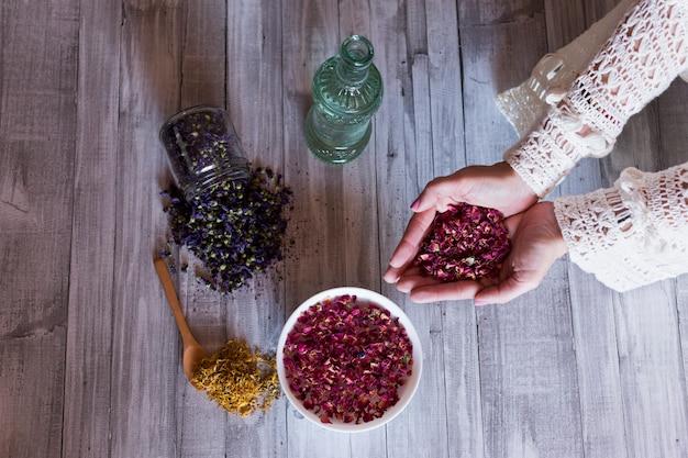 乾燥したバラの葉を保持している女性の手の平面図です。健康的なライフスタイルのコンセプト。屋内。灰色の木製テーブルの背景。黄色のウコン、水とテーブルの上の紫色の種のボウルのボトル。