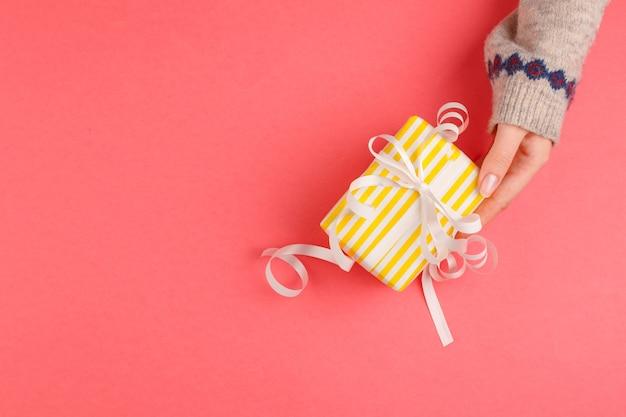 Вид сверху руки женщины, держащей подарочную коробку на розовом фоне