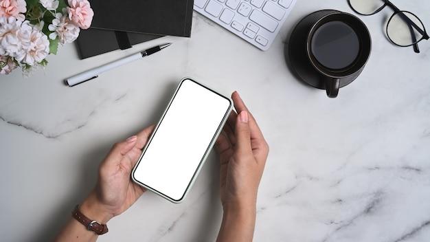 Вид сверху на руки женщины, держащей макет смартфона с белым экраном на мраморном столе.