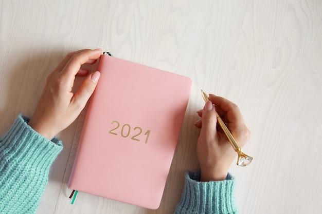 Вид сверху на руки женщины в теплом свитере с дневником 2021 кораллового цвета на столе. планы на будущее и достижения на новый 2021 год. благополучный образ жизни