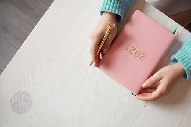 テーブルの上に珊瑚色の2021日記の本と暖かいセーターを着た女性の手の上面図。 2021年の新年の将来の計画と成果。ウェルビーイングライフスタイル