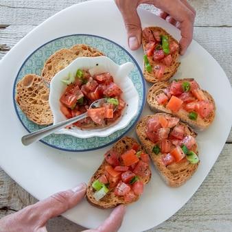 おいしいトマトのイタリアの前菜を準備している女性の手の上面図-ブルスケッタ、トーストしたバゲットのスライス、クローズアップビュー