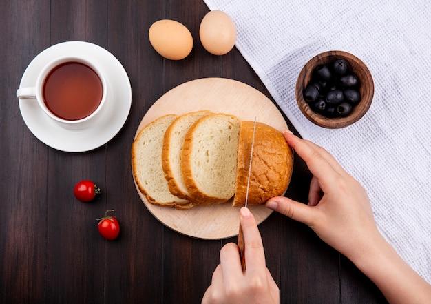 まな板の上にナイフでパンをスライスする女性の手の平面図、木製の表面の布の上にブラックオリーブのボウルとお茶の卵のトマトのカップ