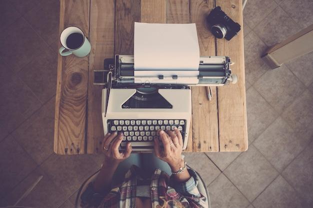 Вид сверху руки женщины, набрав на клавиатуре пишущей машинки на бумаге. женщина печатает на старой клавиатуре пишущей машинки за офисным столом с кружкой кофе и камерой на столе