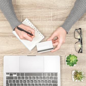 Вид сверху руки женщины с кредитной картой и ноутбуком на столе.