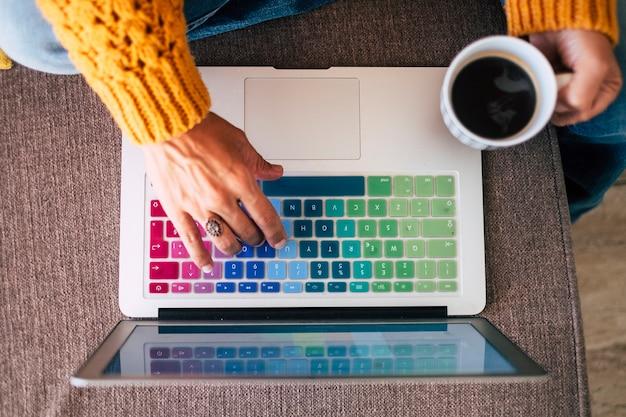 自宅でブラック コーヒーを飲みながらノート パソコンで作業している女性の手のトップ ビュー