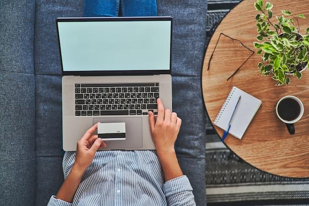 クレジットカードを保持し、コンピューターでオンラインショッピングをしている女性の上面図。