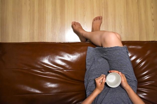 革のソファに座ってカップを保持している女性の平面図は、朝の時間にリラックスします。