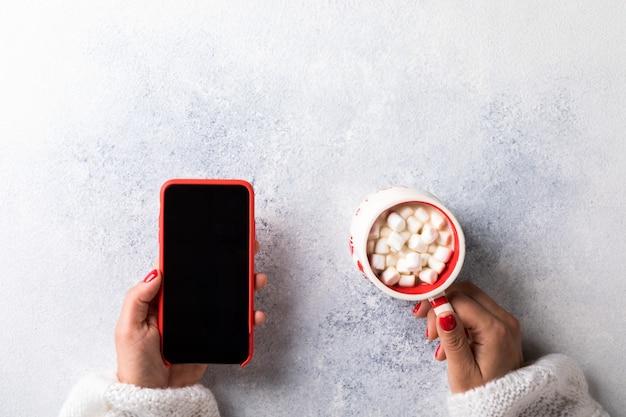マシュマロとスマートフォンでカップを保持している女性の上面図