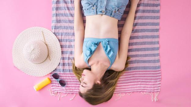 Вид сверху женщина в бикини, спать на полотенце