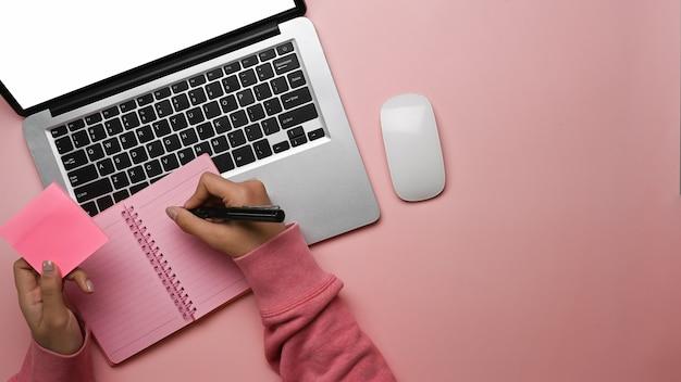 노트북에 메모를 만들고 랩톱 컴퓨터를 사용하는 여자의 상위 뷰