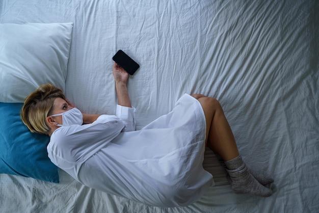 스트레스를 받는 정신 건강과 코로나바이러스를 느끼는 병원에서 침대에 누워 있는 여성 환자의 상위 뷰