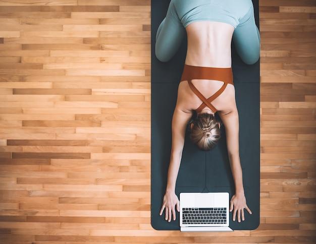 ラップトップとヨガマットでヨガを練習している女性の上面図。女の子は自宅でビデオトレーニングで瞑想とリラックスをしています。デジタルデバイスでのオンラインスポーツクラスまたは瞑想コースの概念。