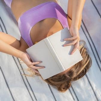 Вид сверху женщины, читающей книгу в купальнике