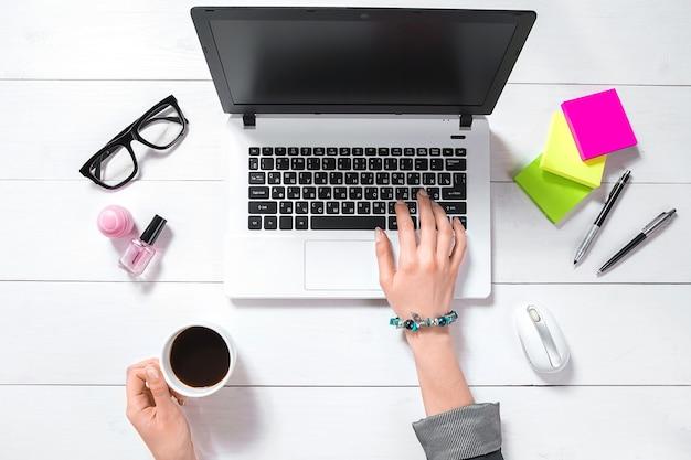 コーヒーカップと白いオフィスのデスクトップに配置されたラップトップのキーパッドで入力する女性の手の上面図。モックアップ