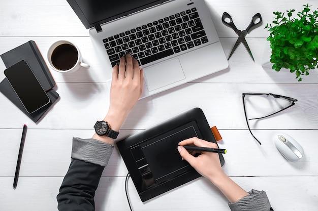 ノートパソコンのキーパッドで入力する女性の手の平面図は、コーヒーカップと白いオフィスのデスクトップに配置されます。
