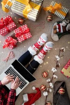 ギフトボックスを保持しているクリスマス休暇でオンラインショッピングの女性の上面図