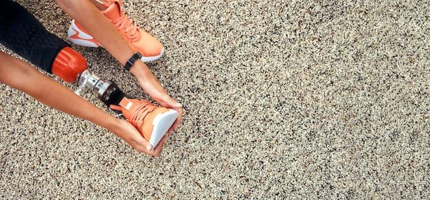 Вид сверху женщины, протягивающей ее протез ноги веб-баннер