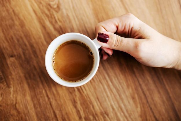 Вид сверху женщины, принимающей свежий утренний кофе арабика из таблицы.