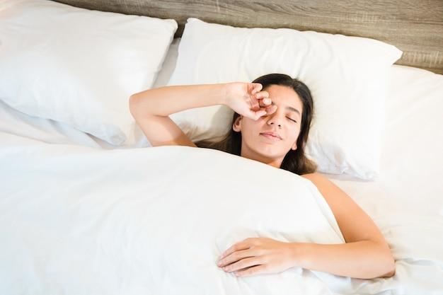 Взгляд сверху женщины просыпая в ее кровати с белым постельным бельем.