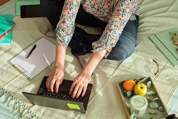 彼女のラップトップ、メモ帳、ティーカップで非公式な環境で働く女性の上面図。リモートワーク、ホームオフィス、フリーランサー、自己隔離の概念