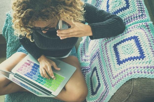 집에서 소파에서 편안한 휴대 전화 통화에 참석하는 동안 다채로운 키보드로 노트북 작업을 하는 여성의 상위 뷰. 편안한 소파에 다리를 꼬고 앉아 노트북과 휴대전화를 사용하는 여성