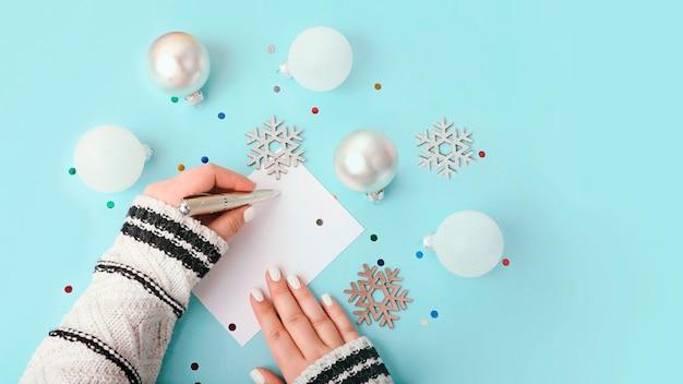 空白のグリーティングカードに書いている女性の上面図。周りの新年の装飾、大きなバナー。