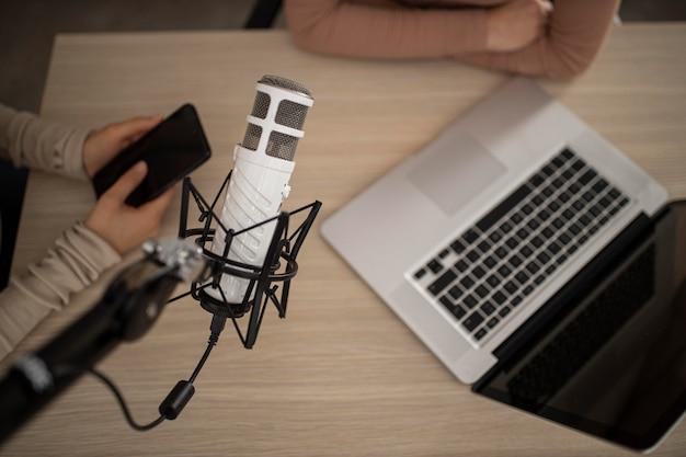 Вид сверху женщин, занимающихся радио вместе с ноутбуком и смартфоном