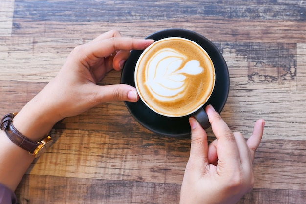 コーヒーカップを持っている女性の手の上面図。