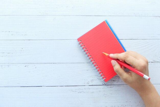 コピースペースのあるメモ帳に鉛筆で手書きする女性の上面図