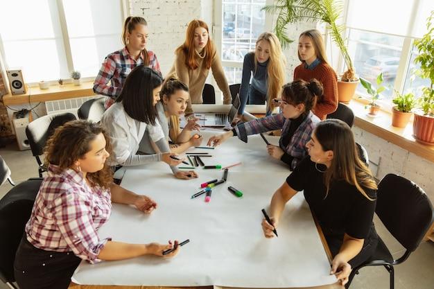 사무실에서 여성의 권리와 평등에 대한 포스터를 준비하는 여성의 상위 뷰. 백인 여성 사업가나 회사원들은 직장 내 문제, 남성의 압력, 괴롭힘에 대해 회의를 합니다.
