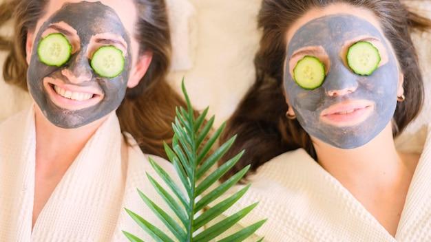 彼らの目にフェイスマスクとキュウリのスライスを持つ女性のトップビュー