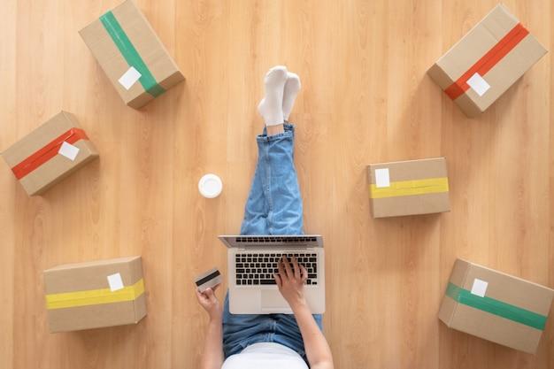 우편 소포와 나무 바닥에 집에서 노트북 컴퓨터를 작동하는 여성의 상위 뷰, 온라인 아이디어 개념 판매