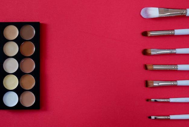 Взгляд сверху косметики женщин на красной предпосылке.