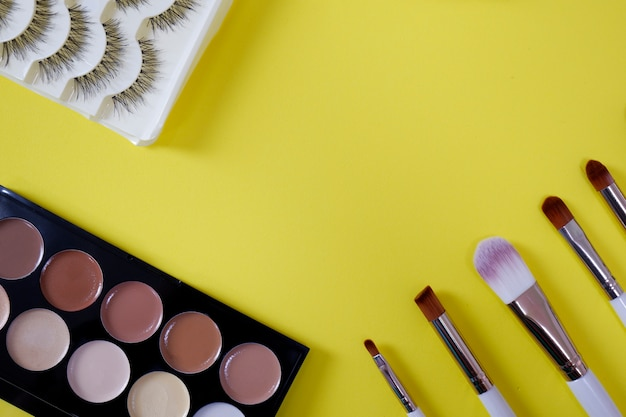 Вид сверху женской косметики на желтом фоне.