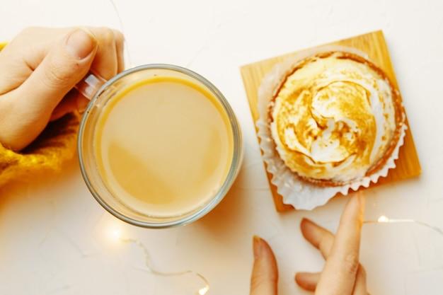 ニットのセーターでコーヒーマグとタルトの女の子に触れている女性の手の上面図は朝食を食べています...