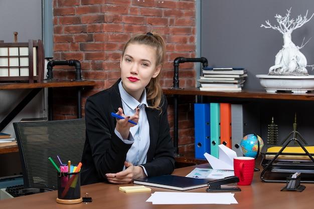 그녀의 책상에 앉아 카메라를 위해 포즈를 취하는 자신감있는 여성 회사원을 궁금해하는 상위 뷰