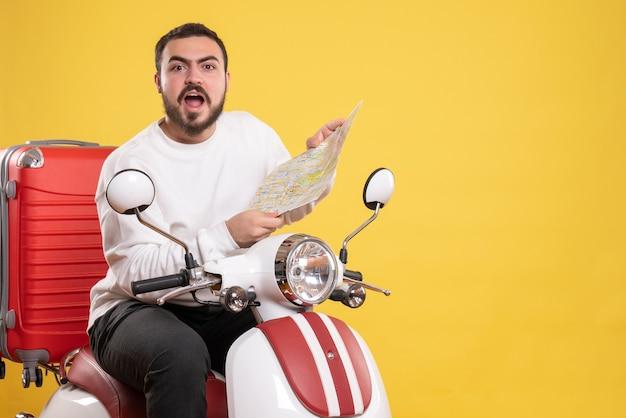 Вид сверху удивленного молодого парня, сидящего на мотоцикле с чемоданом на нем и держащего карту на желтом