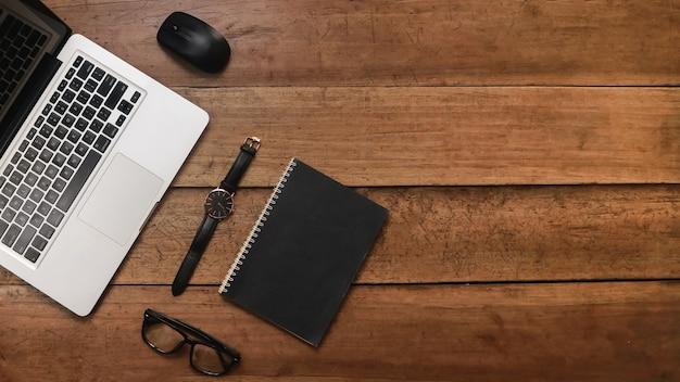 ノートパソコンのメガネとビンテージスケッチブックと木製の背景の上面図