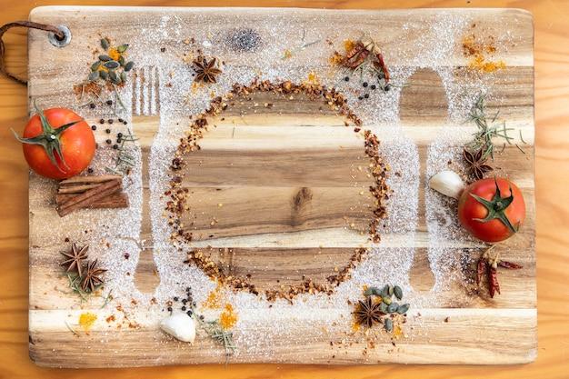木の板ウィットトマト、スパイス、小麦粉のカトラリーの形状のトップビュー