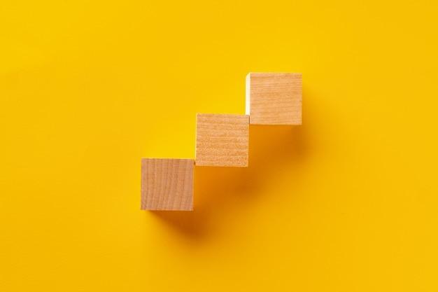 노란색 배경에 나무 큐브의 상위 뷰