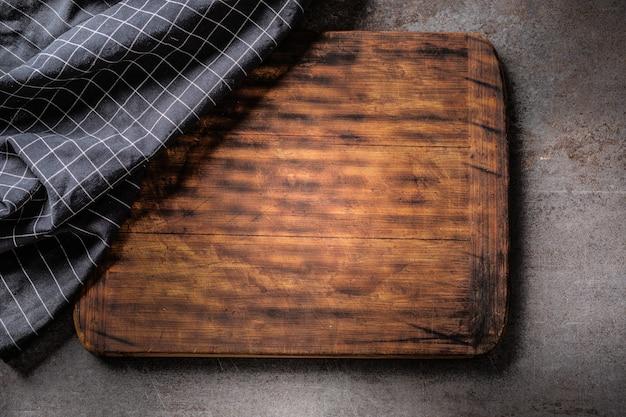 Вид сверху деревянной темно-коричневой винтажной разделочной доски на темном металлическом фоне с частичным покрытием черной клетчатой ткани