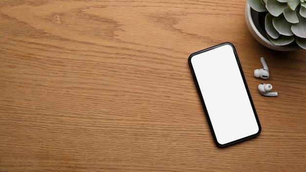 スマートフォン、イヤホン、植木鉢、コピースペースを備えた木製デスクの上面図