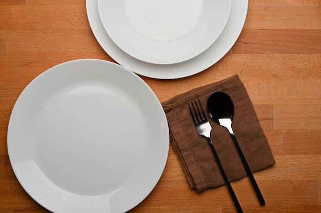 モックアップセラミックプレートカトラリーとナプキンと木製のダイニングテーブルの上面図