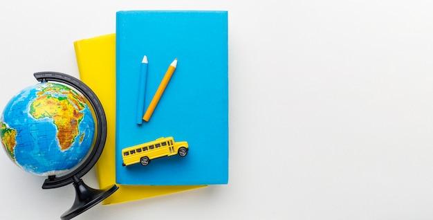 Вид сверху деревянного глобуса с книгами и школьным автобусом