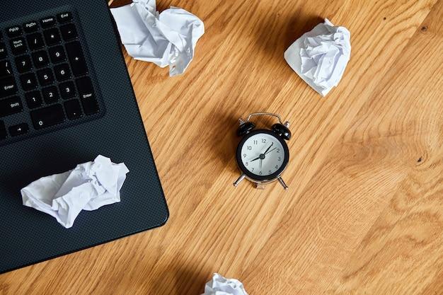 時計付きの木製オフィスデスクの上面図、ノートブック、しわくちゃの紙のボール、考え方を変える、プランb、新しい目標を設定する時間、プラン、