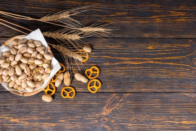 小麦の近くにピスタチオ、古い暗い机の上に散らばった小さなプレッツェルとピーナッツが付いている木の板の上面図。食品および飲料の概念