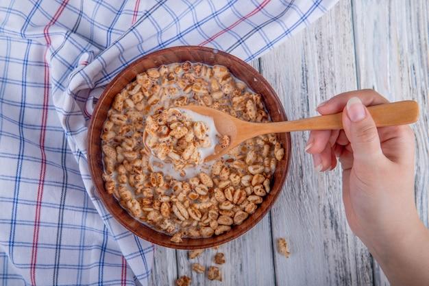 Вид сверху деревянной ложкой и миску с воздушным сладким рисом на деревенском фоне